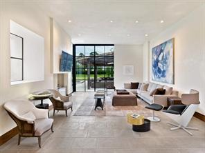 This family room opens to the gourmet kitchen and pool house/outdoor areas. Complete with fireplace for chilly nights.