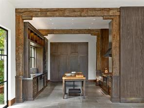 """Stainless Steel, limestone floors and 200 year old farmhouse oak beams with original blacksmith nails give an Old World feel and distinguish the kitchen.  48"""" Sub Zero built in refrigerator and Large walk in pantry are hidden behind oak doors."""