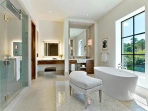 Solid surface soaking tub in the master bath rests beside marble mosaic flooring. Heated floors and steam shower.