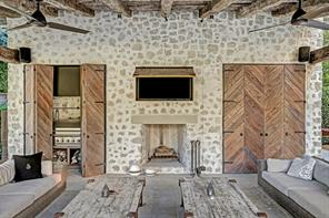 Reclaimed 200 year old farmhouse oak beams, clay roof tiles and stones from the South of France. Geometric design doors conceal television, wet bar with ice maker, refrigerator and DCS built in grill and burner with a vent a hood.