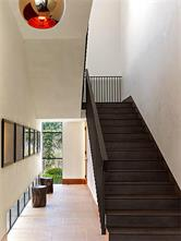 Four of the Five Bedrooms are upstairs, accessed via the foyer stairway. A welded-in-place steel handrail with oiled walnut treads and illuminated by a Tom Dixon pendant.