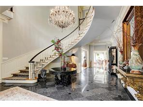 The spacious entry makes quite a statement with it s gleaming marble floors, sparkling chandelier and extreme ceiling height