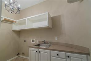 Laundry Room with Wall of Cabinets and Sink is Located on First Floor.