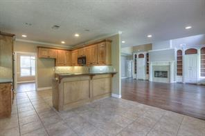 Kitchen has bar seating, black appliances, double ovens, granite and an eating space.