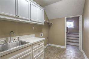 Utility room has both gas and electric dryer connections and a sink & cabinets for storage.