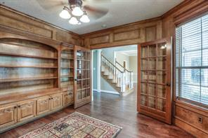 Study has beautiful wood built-ins, french doors and wood flooring.