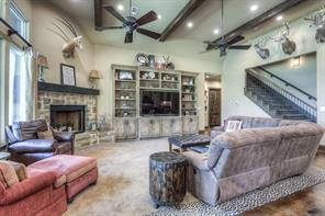 Spacious living room has 2 ceiling fans, gas fireplace, beautiful cedar beams and built-in custom painted shelving.