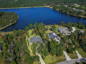 Gorgeous home is situated next to a vacant lot and backs to the stocked beautiful lake. Plenty of room for a pool! Aerial view shows a portion of Majestic Lake, which continues around to the left to the dock and park. Home is furthest left. Make this one yours!