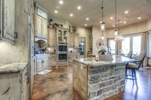 Gorgeous gourmet kitchen with double ovens, built-in fridge, huge stone island with bar seating, under cabinet lighting, plenty of storage space, gas cooktop and beautiful granite.