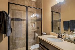 Downstairs guest bathroom with a convenient walk-in shower accented with glass tiles.