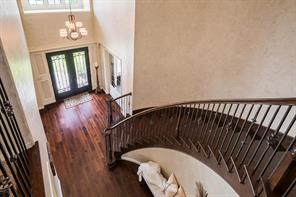 Grand foyer with majestic curved staircase and rich hardwoods. Wrought iron spindles all the way up!