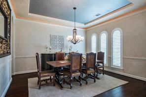 Understated formal dining with plantation shutters. Look up and notice the accent ceiling for a touch of glamor.