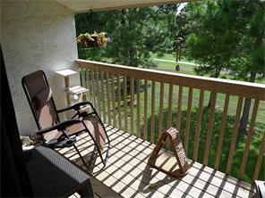 Balcony with serene view of mature tall trees, and golf course.