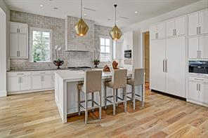 Stunning Kitchen featuring a 9'x6' Island, two large brass pendant light fixtures, and plenty of seating space with additional cabinet storage.