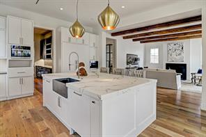 """Behind the island is the Miele 48"""" 6-burner plus griddle gas stove with two ovens and ventilation hood. The Ann Sacks tile backsplash extends all the way to the ceiling."""