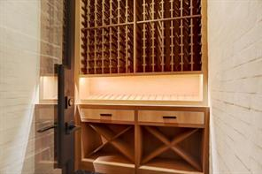 A steel and iron door opens to the climate controlled WINE ROOM with wall to wall built-in wine storage and display racks.