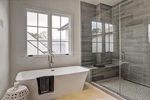 Close view of the oversized freestanding tub and separate shower with rain and wall shower heads.
