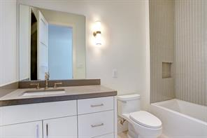BATHROOM 3 has a walk-in shower with glazed subway tile surround.
