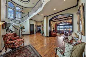Upon stepping into the stunning vestibule, magnificent water views greet guests. Impressive soaring ceilings, gorgeous chandeliers, beautiful gas fireplace and dramatic wooden beam detail enhance the open spaces perfect for entertaining.