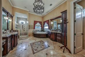 More rich cabinetry, beautifully tiled and oversized multi head shower, large jetted tub, TV space, travertine tile flooring wth mosaic touches. His and her dressing rooms, California style closets are connected to the spa area.