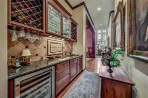 Gorgeous tile mosaic defines Wet bar with wine fridge, bottle & glass storage, display & liquor cabinets. Formal dining, vestibule, kitchen, living and side entrance all have bar access. Truly perfect for entertaining or relaxing!
