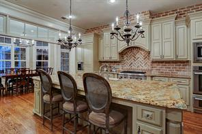 This handsome gourmet kitchen is the focal point down stairs with an exposed brick backsplash, an enormous island with kitchen bar seating, lots of cabinets, cabinet faced Thermador refrigerator, stainless Thermador 4 burner cook top with griddle, convection oven, microwave and warming drawer.