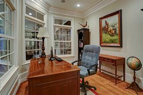 There are actually two downstairs offices. This one enjoys views of the backyard, pool and loggia while the other is located in the mud room and utility room areas in the back of the house which accesses a two-car porte-cochere.