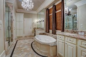 The master bath offers an elegant space with marble floors, a crystal chandelier, granite counters, a glass frame-less shower, His & Her walk-in closets with pull downs and a spa tub as the center piece.