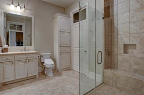 The guest house bathroom offers two huge walk-in closets marble floors, marble counters, and a frameless glass, wheelchair accessible walk-in shower.