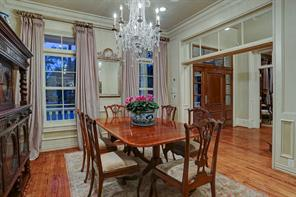 "This banquet style formal dining room lies in the front of the home and is finely appointed with high ceilings, transom doorways, wainscoting, crown molding with an ""egg and dart"" pattern, elegant draperies and 12"" baseboards."