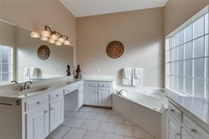 Master bathroom with double sink areas, spa tub, and separate shower.