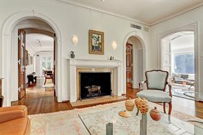 [Living Room]Rejuvenated oak floors, tall ceilings, and creamy plaster walls, enhanced and protected with picture molding, extend through seamlessly-integrated, light-filled formal and informal gathering rooms. In the living room, an exquisitely carved fireplace is flanked by sets of solid-wood doors that open into the den, effectively creating a double parlor.