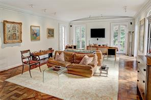 [Den 28 x 17]The den offers a gently bowed ceiling, inlaid oak floor, and a marble fireplace, and overlooks the gardens through arched fixed French doors.