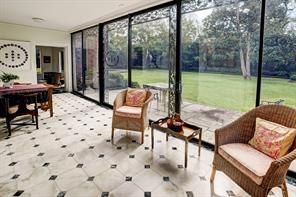 [Sunroom]Tall cased openings from the living room and the den allow easy drift into the adjacent sunroom that overlooks the bluestone patios, gardens, and pool through glass doors framed by wrought iron trellises.