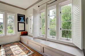 [Study Hub / Office]The original sleeping porch has been converted into a cheery study or reading room with casement windows all around, window seats, and bookcases.
