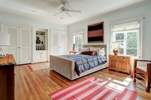 [Secondary Bedroom]En suite bedroom has a hardwood floor, double closets, bookcase/cabinet. Attached, modernized bath retains vintage arts and crafts tile accents.