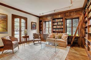 [Library 14 x 14]Tall arched French doors overlook the front gardens. Note rich paneling and floor-to-ceiling bookcases with library ladder.