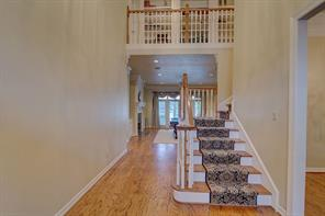 A grand two story foyer greets you upon arrival. There are hardwood floors and tall ceilings throughout. Note the book cases on the upper level.