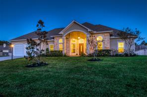Front view of this beautiful newer stucco and stone home with it's large front yard and gently sloping driveway.
