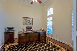 The study is at the front of the home and has a lighted ceiling fan, wood floors, crown molding and double windows with plantation shutters.