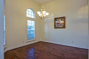 Formal dining room faces the street, has plantation shutters with arched windows above, a lovely chandelier that is brushed nickel and beautiful wood floors.