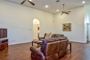Double ceiling fans and extra ceiling lighting show some of the extra features of this delightful home. Again you can see the space at the far end of the living room. Arched door straight ahead leads to the secondary bedrooms and bathroom.