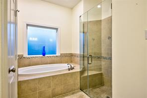 Gorgeous master bathroom with frameless shower and seat, whirlpool tub and neutral tile work adds even more appeal.