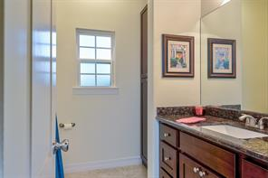 This secondary full bathroom has a tub/shower combination behind the door, commode by window and a built in linen closet is by window on the right.  Beautiful cabinets with granite countertop, brushed nickel hardware and a recessed large sink complete this picture.