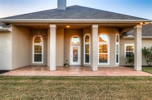 Close up of back porch of this darling home with the bay windows of the breakfast nook on the right.  Grill those steaks outside on this patio!