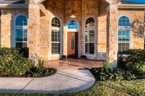 A charming covered porch with patterned and stained concrete, pillars and porch ceiling with cedar beaded board will greet your guests.  The sun setting and angled shadows show that the front of the house is facing Southeast.  The stone is a beautiful color but looks a little different color in this picture than it really is.
