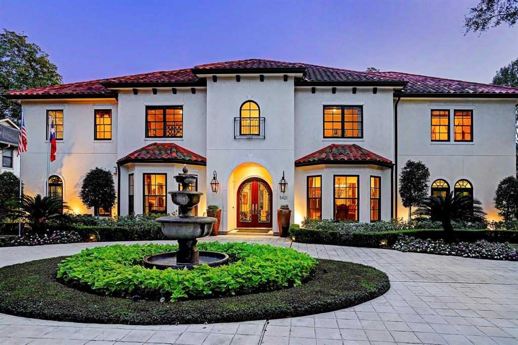 This Mediterranean beauty with a stucco exterior & tile roofs has a large circular driveway with a fountain in the middle that offers plenty of parking for guests.  Notice the lush landscaping and welcoming front entrance!