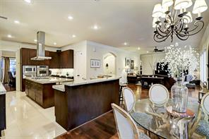 The GOURMET KITCHEN is a chef's dream with a big island with a gas cooktop and powerful vent above, stainless appliances, a plethora of cabinets and drawers, travertine floors, a peninsula that is perfect for multiple bar stools, and a walk-in pantry.