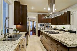 A good view of the double stainless sinks on the left, the refrigerator beyond and the huge island.  This GOURMET KITCHEN has so much prep space for multiple cooks in the kitchen!