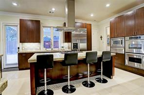Bar stools fit beautifully at the large kitchen ISLAND.  Notice the double convection ovens and built-in microwave with warming drawer below to the right.